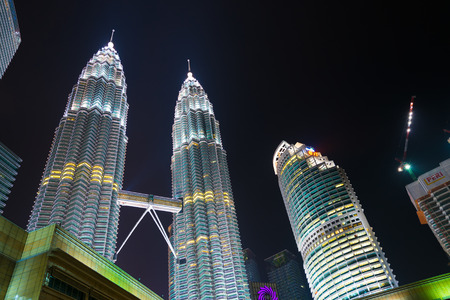 night life: KUALA LUMPUR - JUNE 14, 2016: A night view at skyscrapers including Petronas Towers in the city center. Kuala Lumpur is the national capital and most populous global city in Malaysia.