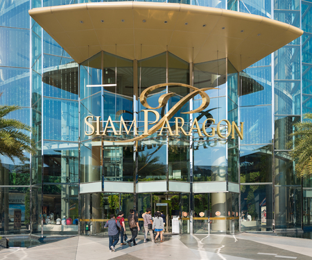 paragon: BANGKOK - MARCH 17, 2016: People walk in and out of the Siam Paragon Shopping mall. It is one of the biggest shopping centres in Asia.