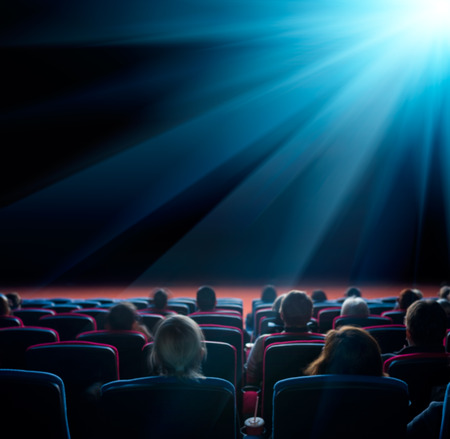 viewers watch shining star at cinema, long exposure, blue glow Stockfoto