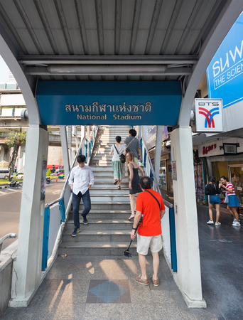 BANGKOK - MARCH 16, 2016: People enter and exit the National Stadium station of Skytrain. The Bangkok Mass Transit System (BTS or Skytrain) is an elevated rapid transit system. Editorial