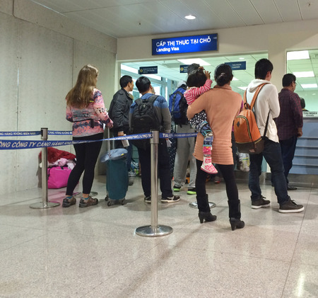 obtain: HO CHI MINH CITY - DEC 17, 2015: Unidentified tourists apply for a visa in the Tan Son Nhat International airport. Holders of a visa letter can obtain a visa at international airports of Vietnam.