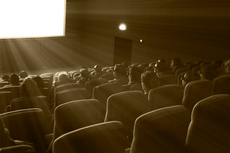 wall watch: viewers watch 3D motion picture in special glasses, sepia toning Stock Photo