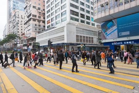 홍콩, 중국 - 2017 년 3 월 16 일 : 많은 사람들이 구룡의 침사추이 (Tsim Sha Tsui) 지역에서 길을 건너고 있습니다. 침사추이 (Tsim Sha Tsui)는 종종 TST로 약칭되