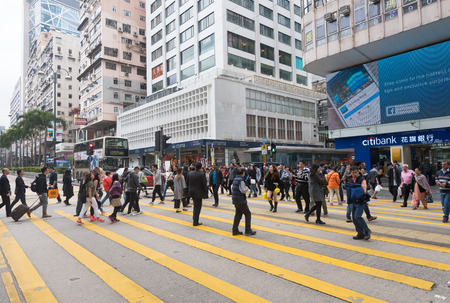 HONG KONG, CHINA - MARCH 16, 2017: A lot of people cross a road in Tsim Sha Tsui area, Kowloon. Tsim Sha Tsui, often abbreviated as TST, is an urban area in southern Kowloon, Hong Kong.