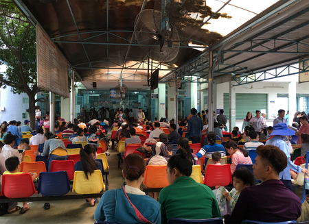 HO CHI MINH CITY, VIETNAM - JULY 2017: A lot of people sitting in the lobby of the Kids Hospital in Ly Thai To Street wait to register to have doctors consultation.