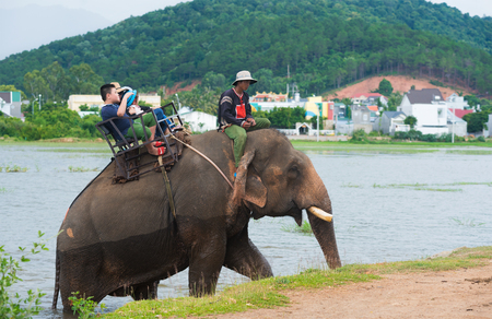 LIEN SON, VIETNAM - JUNE 30 2017: Unidentified tourists ride an elephant at a lake. Lien Son is a commune and village in Dak Lak Province, in northeastern Vietnam. Sajtókép