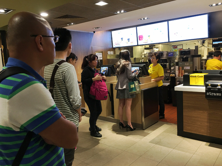 HONG KONG - MARCH, 2017: People stand in queue at a McDonalds in Peking Road. McDonalds Corporation is the worlds largest chain of hamburger fast food restaurants serving 68 mln clients daily Editorial