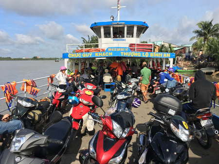 daily life: HO CHI MINH, VIETNAM - JULY 4, 2017: A ferry brings commuters and vehicles to Binh Khanh quay from the opposite bank of the Nha Be River. Ho Chi Minh City is the largest city in Vietnam (9 mln).
