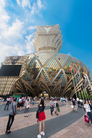 MACAU - SEPTEMBER 2017: People in front of the Grand Lisboa hotel, the tallest building in Macau and the most distinctive part of its skyline