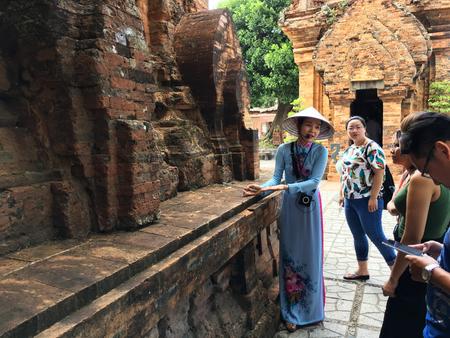 NHA TRANG, VIETNAM - OKTOBER 2017: Eine nicht identifizierte vietnamesische Frau führt eine Führung für eine Gruppe Touristen am Ponagar Cham-Tempelturm des 8. Jahrhunderts durch Standard-Bild - 91156124