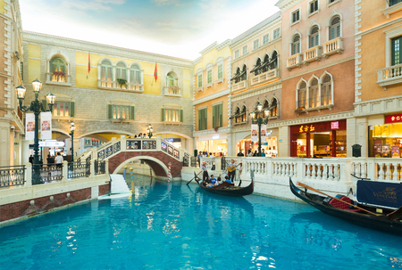 MACAU, CHINA - SEPT 15, 2017: A gondolier drives tourists at the Venetian Macao. It is a luxury hotel and casino resort in Macau owned by the American Las Vegas Sands company
