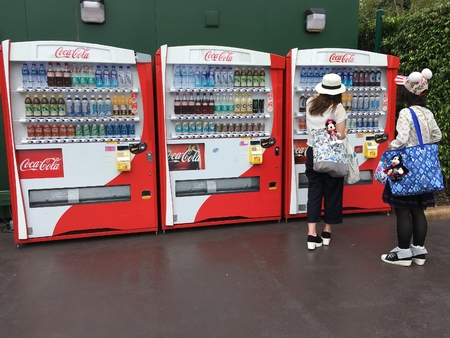 HONG KONG - SEPTEMBER 2017: Two unidentified young women buy Coca Cola drinks near Hong Kong Disneyland. The theme park is located on reclaimed land in Pennys Bay, Lantau Island.