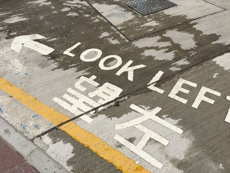 look left reminding sign for pedestrians on a Hong Kong road, where thereis left driving Reklamní fotografie