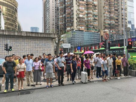 MACAU - SEPTEMBER 16, 2017: Many people stand at a pedestrian crossing downtown Macau. It is a major resort city and the top destination for gambling tourism.