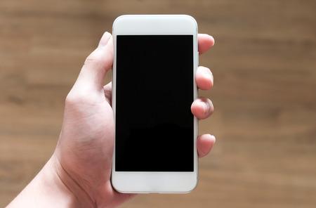 垂直方向の白のスマート フォンを持っている人間の手 写真素材