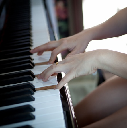 Close up of girl hands playing the piano photo