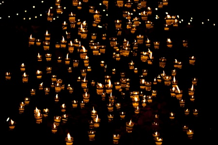 lit: Group of burning candles on black background Stock Photo