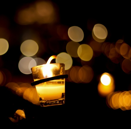 votive: yellow candle burning in the dark Stock Photo