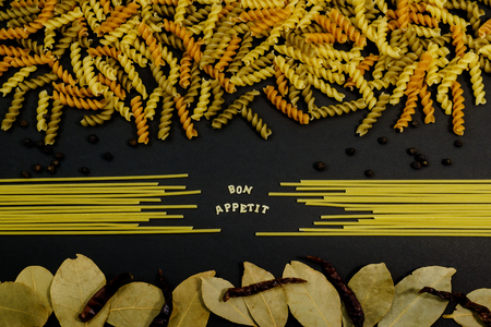 health concern: Bon Appetit sign spelled using pasta letter with other ingredients on black