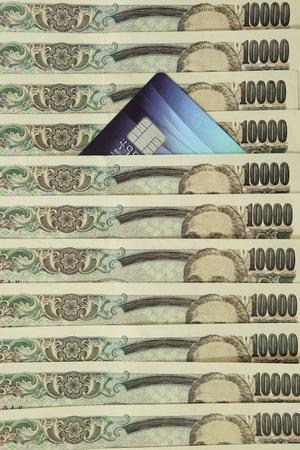 Credit card among heap of cash in Japanese Yen