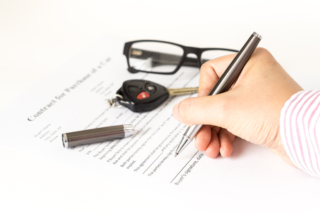 sell car: Man signing a car purchase contract on white