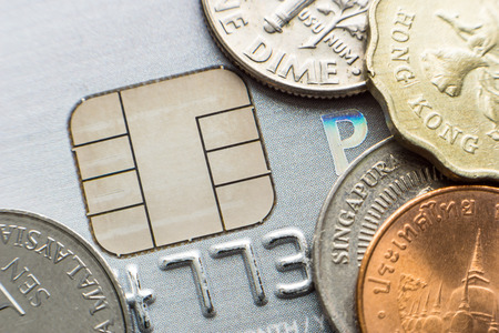 international bank account number: Microchip credit card and coins from different currencies close-up Stock Photo