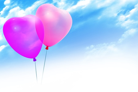 Colored balloons in a heart shape on blue sky photo