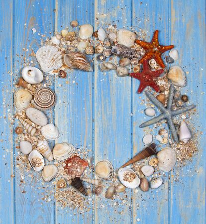 Top view of seashells and starfishes on blue wooden planks background. Creative flat lay concept of summer. Archivio Fotografico