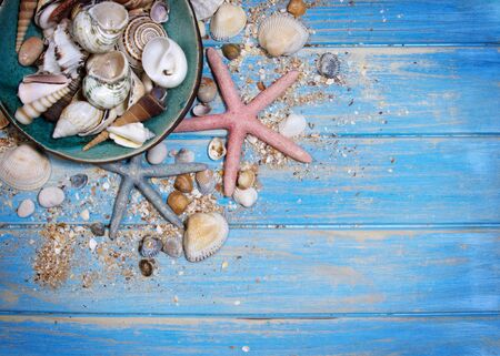 Top view of seashells and starfishes on blue wooden planks and ceramic plate with shells. Creative flat lay concept of summer Archivio Fotografico