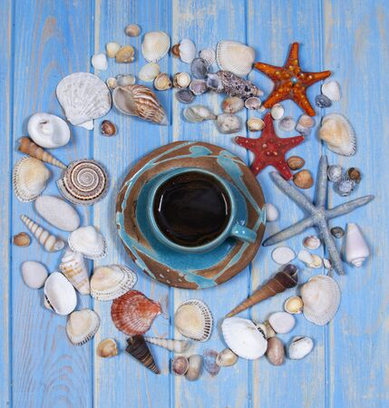 Top view of seashells and starfishes with a cup of coffee