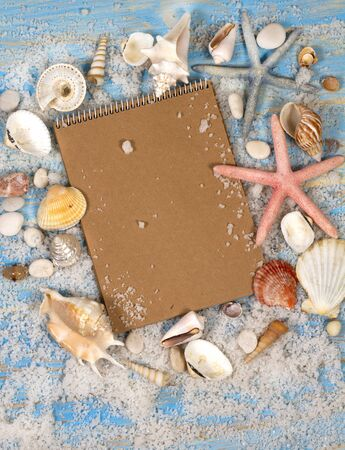 Open notebook with seashells and starfish. Planning summer holidays, travel and vacation background.