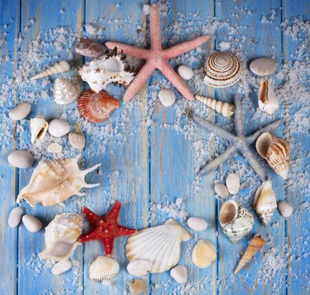 Round frame of seashells and starfishes on blue wooden planks background. Creative flat lay concept of summer