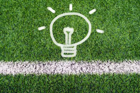 Idea light bulb hand drawing on soccer field grass photo