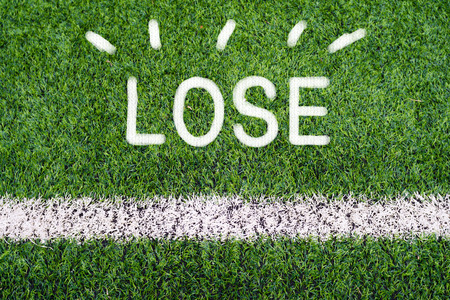 LOSE hand writing text on soccer field grass photo