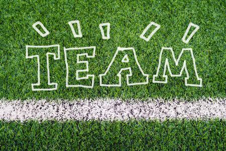 TEAM hand writing text on soccer field grass photo