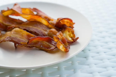 greasy: Cooked Greasy Bacon on white plate