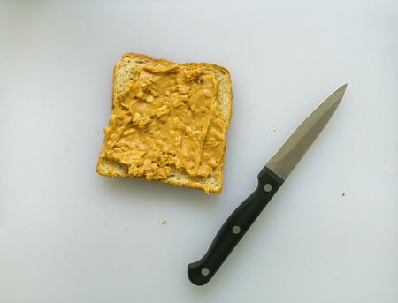 allergic ingredients: peanut butter toast with a knife on white cutting board Stock Photo