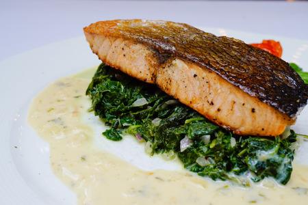 salmon steak: Salmon steak on spinach with white lemon sauce Stock Photo
