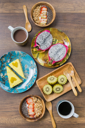 chia seed: Breakfast set on  wooden table : Granola with strawberry and chia seed, dragon fruit, kiwi, pumpkin cake, hot coffee, hot chocolate flat lay