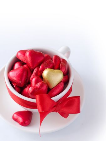 White cup with saucer with red and gold chocolate hearts and red ribbon. Photo on a white background Stock Photo - 6204295