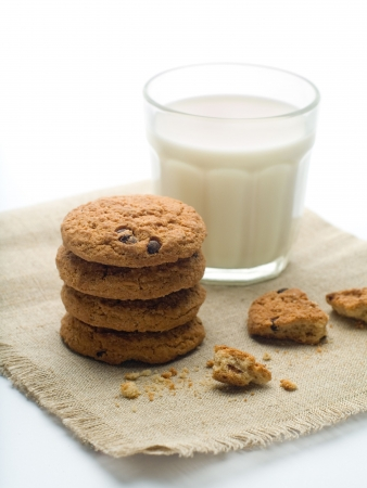 milk and cookies: Glass of milk with oatmeal cookies on napkin. A photo on white background