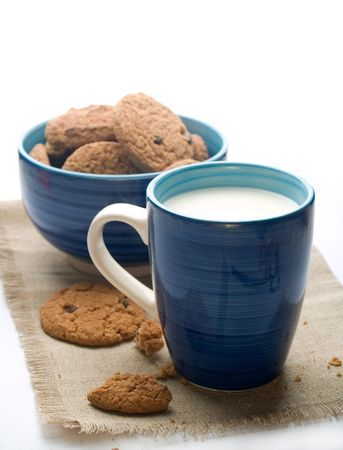 Bowl of cookies with mug of milk on napkin. A photo on white background photo