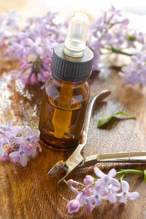 toiletry: Massage oil for nail and manicure scissors. Lilac on background. Could be a generic toiletry.