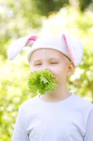 Portrait of the little boy in a cap with  bunny ears and eating lettuce Stock Photo - 7065050