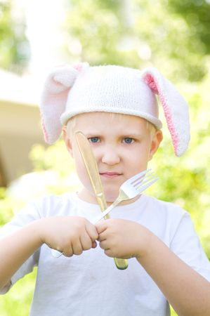 Portrait of the malicious little boy in a cap with  bunny ears  photo