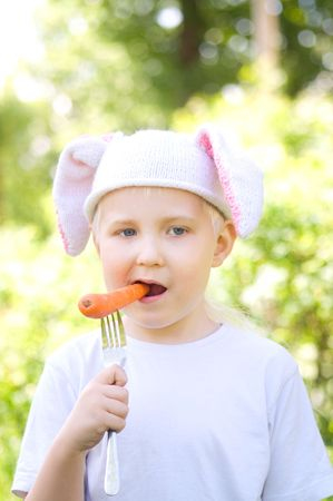 Portrait of the little boy in a cap with  bunny ears and eating carrot photo