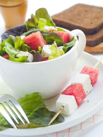 sliced watermelon: Salad from lettuce, watermelon and feta in cup Stock Photo