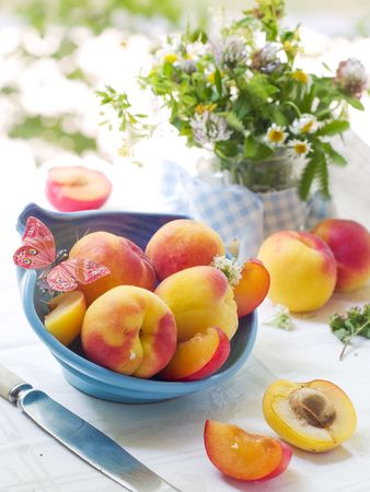 butterfly knife: Fresh apricot in bowl with butterfly and wild flowers on background Stock Photo
