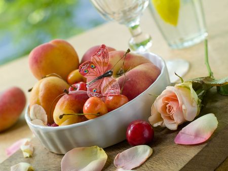 Fresh apricots, plums, cherry in bowl with rose and butterfly  on foreground Stock Photo - 7444716