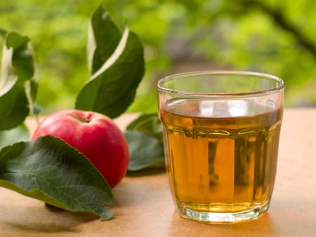 Glass of apple juice with apples on the background.  photo